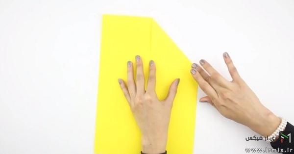 تا زدن گوشه های بالای کاغذ زرد رنگ